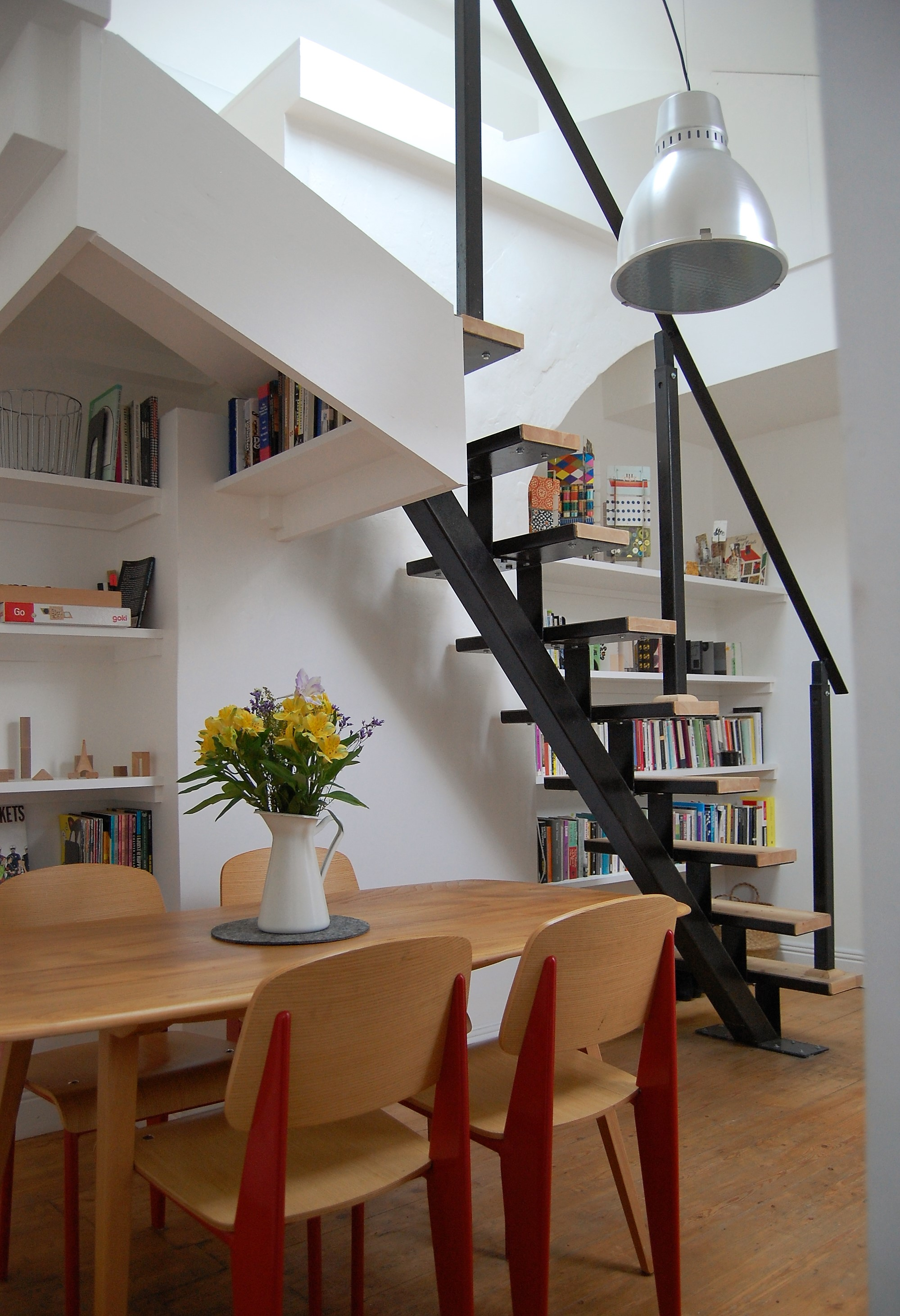 Dining Space With Stairs and Display Wall