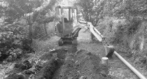Image of digger breaking ground in garden of protected structure
